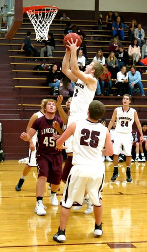 Photo by Randy Moll Gentry senior, Jarod Cousins, attempts a shot for two under the basket in play against the Lincoln Wolves on Monday, Dec. 15, at Gentry High School.