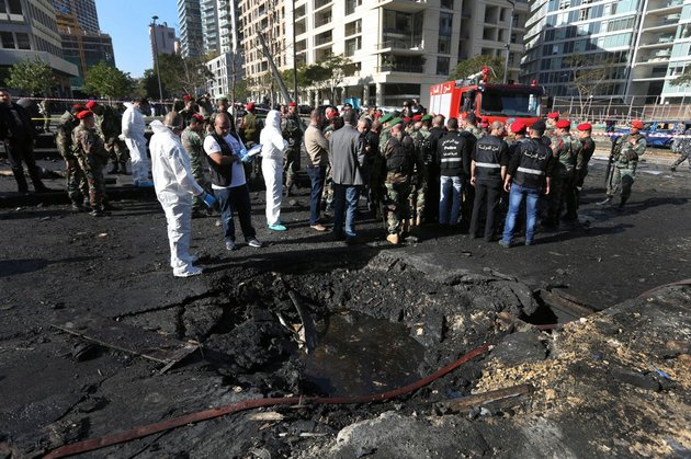 lebanese-army-investigators-in-white-coveralls-stand-next-to-a-blast-crater-at-the-scene-of-an-explosion-in-beirut-lebanon-friday-dec-27-2013-a-powerful-car-bomb-tore-through-a-business-district-in-the-center-of-the-lebanese-capital-friday-killing-mohammed-chatah-a-prominent-pro-western-politician-and-at-least-five-other-people