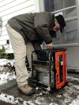 John Johnson, of East Lansing, Mich., works to hook up a generator he borrowed from a neighbor to heat his house on Friday, Dec. 27, 2013. As of Friday morning, Johnson had been without power since Sunday because of an ice storm. (AP Photo/David Eggert)