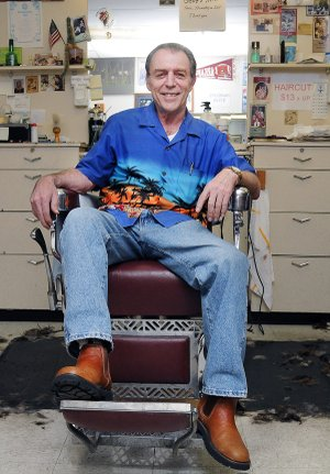 Gene Wolf sits in his barber shop Thursday, Dec. 19, 2013, at 111 W. Central Ave. in Bentonville. Wolf, who has been cutting hair at Gene's Barber Shop for 20 years, will be retiring at the end of the month after 46 years in the business.