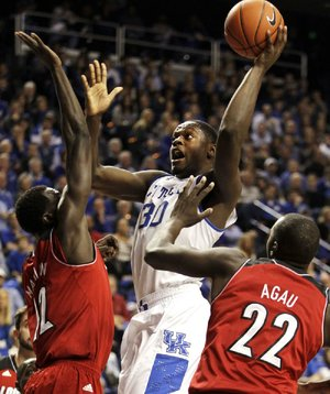 Kentucky's Julius Randle (center) shoots between Louisville's Mangok Mathiang (left) and Akoy Agau during the second half of Saturday's game in Lexington, Ky. Randle scored 17 points in the first half and finished with 21 as Kentucky won 73-66.