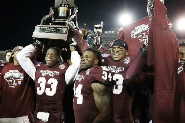 Mississippi State's Kivon Coman (33), Josh Robinson (34) and Michael Hodges celebrate with the Liberty Bowl trophy after defeating Rice 44-7 on Tuesday in Memphis. It was the lopsided outcome in the game's 55 years.