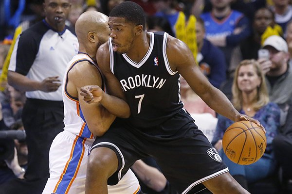 Brooklyn Nets guard Joe Johnson (7) drives against Oklahoma City Thunder guard Derek Fisher during the third quarter of an NBA basketball game in Oklahoma City, Thursday, Jan. 2, 2014. The Nets won 95-93. (AP Photo/Sue Ogrocki)