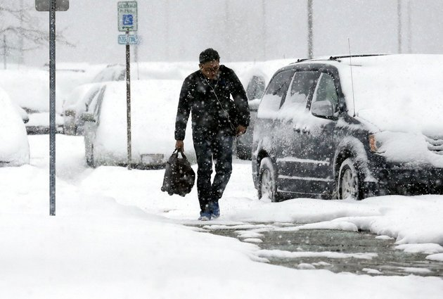 a-traveler-walks-in-the-economic-parking-lot-at-ohare-international-airport-in-chicago-on-thursday-jan-2-2014-another-one-to-three-inches-of-snow-could-fall-across-the-chicago-metro-area-thursday-with-even-more-falling-in-the-southern-part-of-the-region-according-to-the-national-weather-service