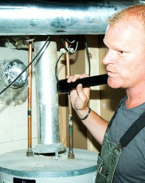 AT HOME for release DECEMBER 2013 DESIGN SCHOOL Caption 02: Author and contractor Mike Holmes notes problems with the exhaust venting from a gas water heater, a critical problem that would be caught during a thorough home inspection.