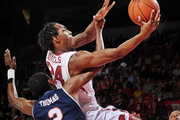 Arkansas forward Michael Qualls is fouled by Hyjii Thomas as he drives to the basket in the first half at Bud Walton Arena in Fayetteville on Saturday Jan. 4, 2013.