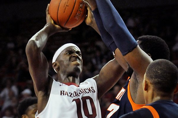 Arkansas' Bobby Portis attempts a shot while being guarded by UT Martin's Pierre Mopo during the first half of the basketball game in Bud Walton Arena in Fayetteville on Thursday December 19, 2013.