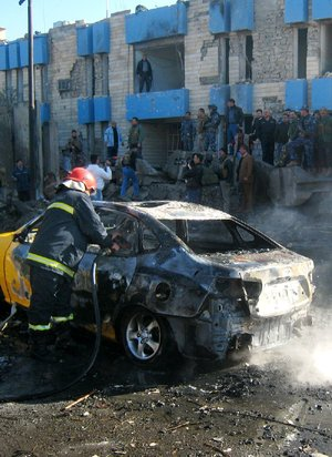 An Iraqi firefighter hoses down a car that caught fire Tuesday after a truck loaded with explosives rammed into a police station in Kirkuk.
