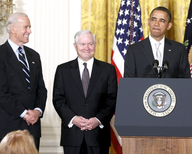 president-barack-obama-stands-in-the-east-room-of-the-white-house-in-washington-with-from-left-vice-president-joe-biden-and-outgoing-defense-secretary-robert-gates-in-this-april-28-2011-file-photo