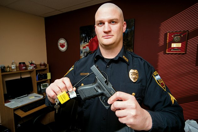 steve-hernandez-public-information-officer-for-the-searcy-police-department-shows-one-of-the-free-project-childsafe-gun-locks-installed-on-a-pistol