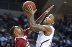 Texas A&M's Fabyon Harris, right, jumps to the hoop against Arkansas' Rahsad Madden during the first half of an NCAA college basketball game in College Station, Texas, Wednesday, Jan. 8, 2014. (AP Photo/Bryan College Station Eagle, Stuart Villanueva)