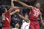 Arkansas' Rashad Madden, left, and Moses Kingsley (33) block the shot of Texas A&M's Shawn Smith during the first half of an NCAA college basketball game in College Station, Texas, Wednesday, Jan. 8, 2014. (AP Photo/Bryan College Station Eagle, Stuart Villanueva)