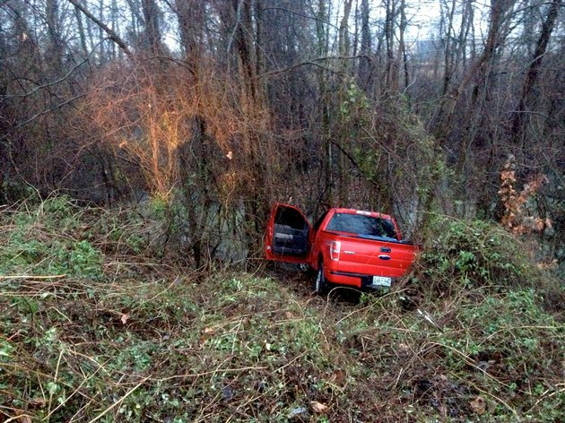 a-pickup-sits-crashed-in-a-wooded-area-after-sliding-friday-jan-10-2014-off-a-wet-interstate-440-in-little-rock