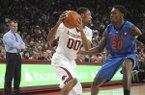 Arkansas guard Rashad Madden (00) looks for room while being guarded by Florida guard Michael Frazier II (20) as Florida coach Billy Donovan, left, watches in Fayetteville, Ark. during an NCAA college basketball game Saturday, Jan. 11, 2014. Florida won 84-82 in overtime. (AP Photo/David Quinn)