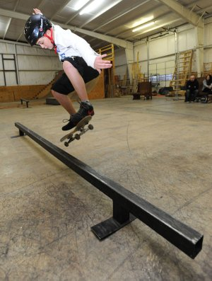 Dante Gales, 10, of Harrison leaps to ride along a metal rail while skating Friday, Jan. 10, 2014, at The Skate Station in Fayetteville.