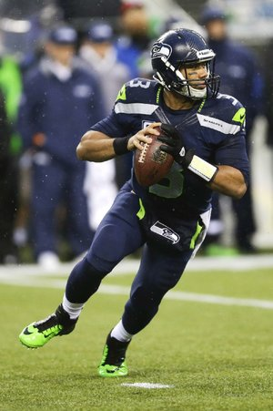 Seattle Seahawks quarterback Russell Wilson rolls out during the second half of an NFC divisional playoff NFL football game against the New Orleans Saints in Seattle, Saturday, Jan. 11, 2014. (AP Photo/Ted S. Warren)
