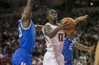 Arkansas guard Fred Gulley III (12) weaves to the basket through Kentucky forward Julius Randle, (30), and guard Aaron Harrison, (2), during the first half of an NCAA college basketball game, Tuesday, Jan. 14, 2014, in Fayetteville, Ark. (AP Photo/Gareth Patterson)