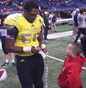 Offensive lineman Brian Wallace Jr. signs an autograph for a young fan after the U.S. Army All American game.