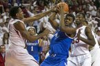 Kentucky center Dakari Johnson, center, is hit under the basket by Arkansas forward Coty Clarke, left, during the first half of an NCAA college basketball game on Tuesday, Jan. 14, 2014, in Fayetteville, Ark. (AP Photo/Gareth Patterson)