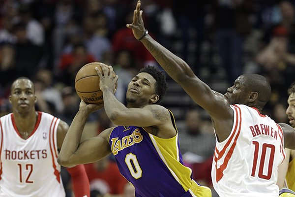 Los Angeles Lakers' Nick Young (0) looks to pass the ball past Houston Rockets' Ronnie Brewer (10) as Rockets' Dwight Howard (12) looks on in the second half of an NBA basketball game on Wednesday, Jan. 8, 2014, in Houston. The Rockets won 113-99. (AP Photo/Pat Sullivan)