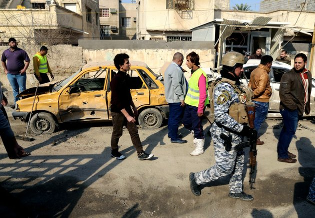 civilians-and-security-forces-gather-at-the-site-of-a-car-bomb-attack-near-the-technology-university-in-sinaa-street-in-downtown-baghdad-on-wednesday-jan-15-2014-a-wave-of-bombings-across-iraq-striking-busy-markets-and-a-funeral-north-of-baghdad-killed-tens-of-people-wednesday-authorities-said-as-the-country-remains-gripped-by-violence-after-al-qaida-linked-militants-took-control-of-two-cities-in-western-anbar-province