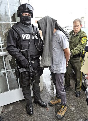 Police in Bennington, Vt., take a suspect into custody in January 2013 during a sweep that rounded up dozens of drug suspects in southwestern Vermont. The state ranks as one of the top 10 for the abuse of illicit drugs.