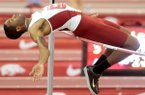 Arkansas senior Anthony May attempts to clear the bar in the high jump during a dual meet against Texas on Friday, Jan. 17, 2014, at the Randal Tyson Track Center in Fayetteville.