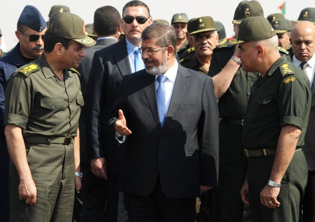 file-in-this-wednesday-oct-10-2012-file-image-then-egyptian-president-mohammed-morsi-center-speaks-with-minister-of-defense-lt-gen-abdel-fattah-el-sissi-left-at-a-military-base-in-ismailia-egypt-the-countrys-ousted-islamist-president-and-24-other-politicians-media-personalities-activists-and-lawyers-will-be-tried-on-charges-of-insulting-the-judiciaryap-photoegyptian-presidency-file