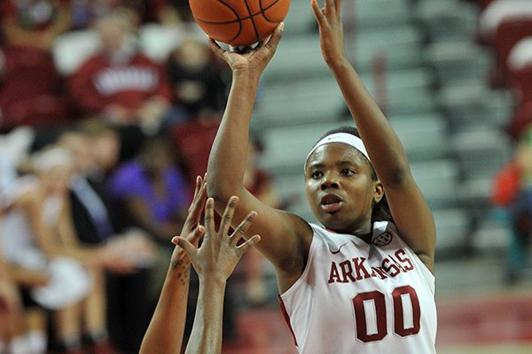 Arkansas forward Jessica Jackson drives to the hoop past Ole Miss defender Tia Faleru in the first half of Sunday afternoon's game at Bud Walton Arena in Fayetteville.