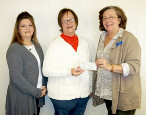 Photo by Randy Moll Lonnie Moll, president of the Gentry Lions Club, presents a check for $1,500 from the Lions Club to the Gentry School District. Receiving the check is Myra Welch, special education secretary for the district, and Angie Dennis, special education director. The check was to pay for half the cost of a VisioBook to assist a vision-impaired student at the intermediate school.