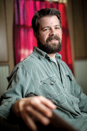 Justin Hubbard of Russellville sits in a pew in the Simple Truth Church, the Atkins church that he pastors. His late great-grandfather pastored a church in the same building for many years, but the family put it up for sale. Hubbard's grandmother, Linda Lewis, bought the building after Hubbard told her he felt called to preach.