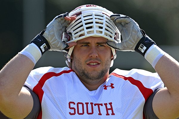 South Squad center Travis Swanson of Arkansas (64) puts on his helmet during Senior Bowl practice at Fairhope Municipal Stadium, Monday, Jan. 20, 2014 in Fairhope, Ala. (AP Photo/G.M. Andrews)