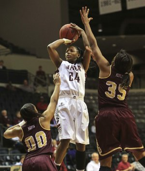 UALR guard Taylor Gault shoots over Texas State defenders Kaylan Martin (left) and Erin Peoples (right) during Wednesday night's game at the Jack Stephens Center in Little Rock. Gault finished with a game-high 23 points in the Trojans' 77-70 victory.