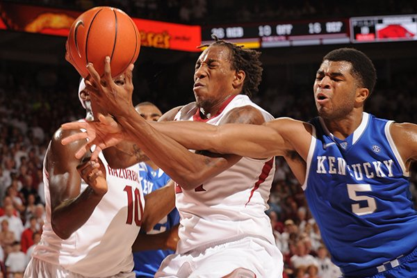 Arkansas guard Michael Qualls, center, and Kentucky guard Andrew Harrison (5) reach for a loose ball during overtime Tuesday, Jan. 14, 2014, in Bud Walton Arena in Fayetteville.