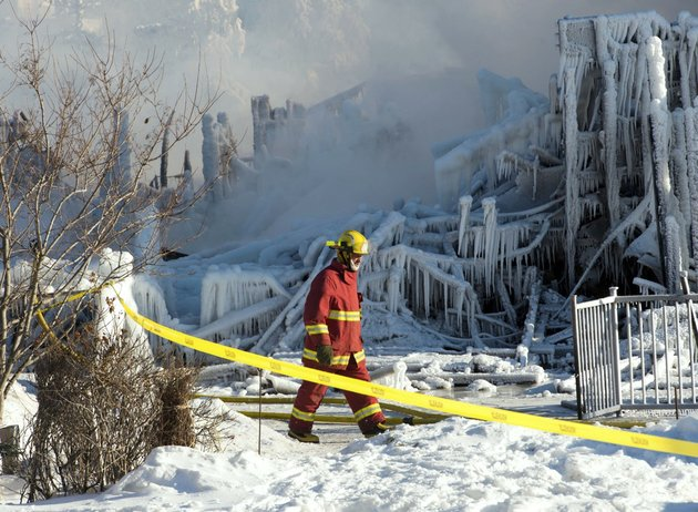 a-firefighter-walks-past-the-rubble-where-fire-destroyed-a-a-seniors-residence-in-lisle-verte-quebec-on-thursday-jan-23-2014-the-fire-in-the-52-unit-complex-broke-out-about-1230-am-in-lisle-verte-about-140-miles-northeast-of-quebec-city