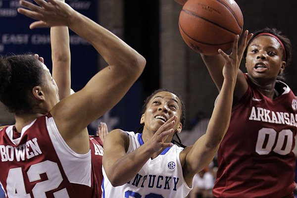 Kentucky's Kastine Evans (32) shoots between Arkansas' Jhasmin Bowen (42) and Jessica Jackson (00) during the second half of NCAA college basketball game, Sunday, Jan. 26, 2014, in Lexington, Ky. Kentucky won 68-58. (AP Photo/James Crisp)