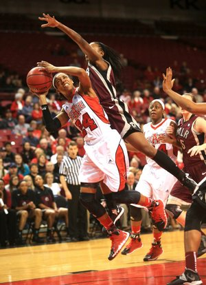 Arkansas State guard Aundrea Gamble (24) is fouled on her way to the basket by UALR guard Taylor Gault during Saturday's game at the ASU Convocation Center in Jonesboro. Gamble finished with 27 points as the Red Wolves beat the Trojans 77-45.