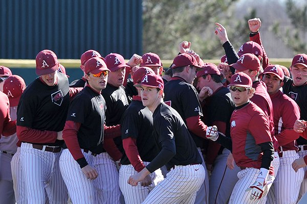 The University of Arkansas baseball team breaks out of their huddle after warm ups to begin the first practice of the season Friday afternoon at Baum Stadium in Fayetteville.