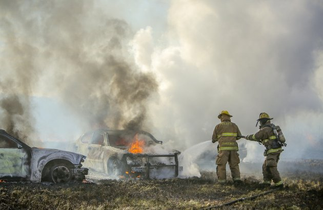 north-little-rock-firefighters-put-out-remaining-flames-inside-two-police-cars-that-burned-to-the-ground-along-with-the-truck-that-the-officers-pursued-in-a-field-behind-alliance-parts-warehouse-at-600-fiber-optic-dr-in-north-little-rock-on-monday-afternoon-the-driver-of-the-truck-led-police-from-multiple-jurisdictions-on-a-chase-that-started-in-grant-county-and-ended-with-the-suspect-running-on-foot-heat-from-the-vehicles-on-the-dry-grass-in-the-field-purportedly-started-the-fire-which-spread-over-10-20-acres-before-being-contained