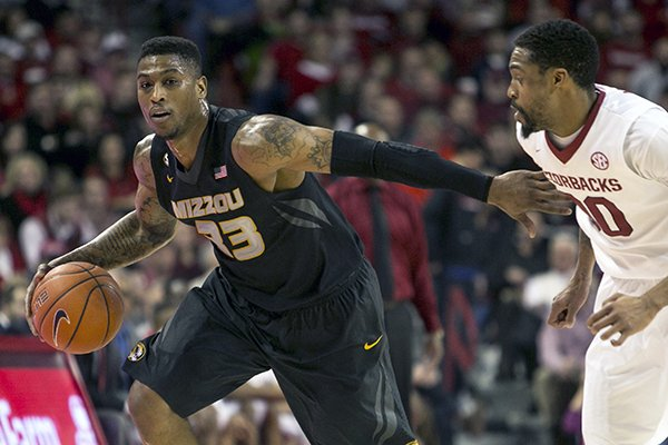 Missouri guard Earnest Ross (33) maneuvers past Arkansas guard Rashad Madden (00) during the second half of an NCAA college basketball game on Tuesday, Jan. 28, 2014, in Fayetteville, Ark. Missouri won 75-71. (AP Photo/Gareth Patterson)