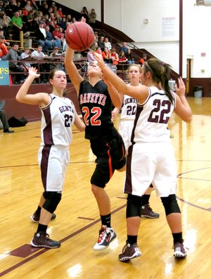 Photo by Randy Moll Gravette s Samantha Pruitt attempts a shot under the basket, surrounded by Gentry players Jordan Olds (#23), Aspen Cripps (#22) and Mallory Morris (#20).