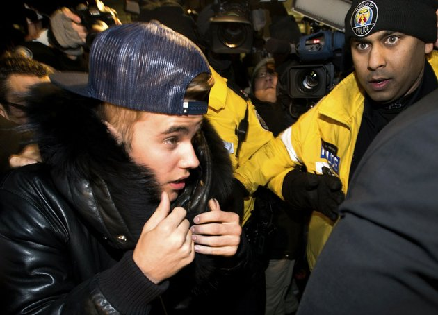 canadian-musician-justin-bieber-is-swarmed-by-media-and-police-officers-as-he-turns-himself-in-to-city-police-for-an-expected-assault-charge-in-toronto-on-wednesday-jan-29-2014-a-police-official-said-the-charge-has-to-do-with-an-alleged-assault-on-a-limo-driver-in-december