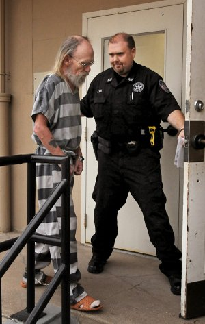 An officer from the Benton County Sheriff's Office escorts John Guerra into the Benton County Courthouse Annex in Bentonville for a bond hearing on Friday January 31, 2014.