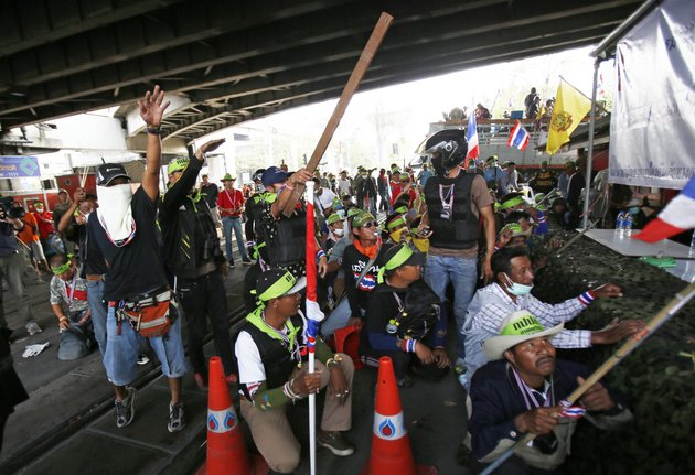 anti-government-protesters-try-to-antagonize-government-supporters-during-a-gun-fight-bangkok-thailand-saturday-feb-1-2014-gunfire-rang-out-at-a-major-intersection-in-thailands-capital-on-saturday-as-clashes-between-protesters-and-government-supporters-erupted-on-the-eve-of-tense-nationwide-elections-at-least-seven-people-are-reported-wounded-including-an-american-photojournalist-ap-photowally-santana