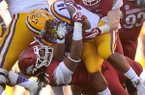 LSU running back Terrence Magee is taken down by Arkansas defenders Darius Philon and Brooks Ellis in the 2nd quarter of a Nov. 29, 2013 game at Tiger Stadium in Baton Rouge, La.