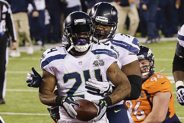 Seattle Seahawks' Marshawn Lynch (24) celebrates with teammate Alvin Bailey after scoring a touchdown during the first half of the NFL Super Bowl XLVIII football game against the Denver Broncos Sunday, Feb. 2, 2014, in East Rutherford, N.J. (AP Photo/Chris O'Meara)