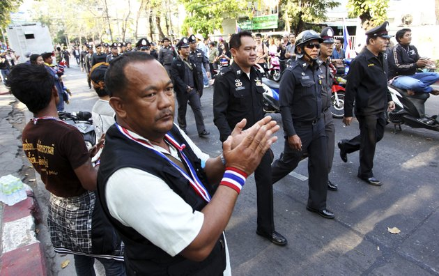 anti-government-protesters-clap-hands-as-thai-policemen-walk-in-to-take-position-between-pro-and-anti-elections-group-at-dindaeng-district-office-in-bangkok-thailand-sunday-feb-2-2014-thailands-tense-national-election-got-underway-sunday-with-protesters-forcing-the-closure-of-several-polling-stations-in-the-capital-amid-fears-of-more-bloodshed-a-day-after-gun-battles-in-bangkok-left-seven-people-wounded-ap-photoapichart-weerawong