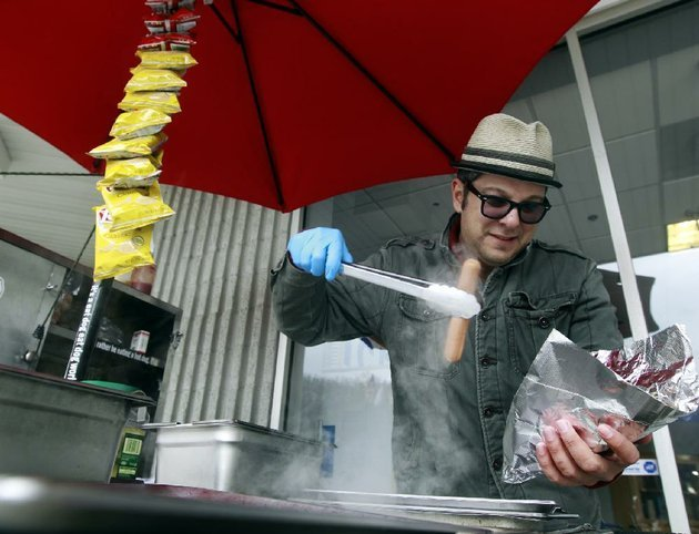 in-this-march-7-2013-photo-mike-juiliano-known-as-hot-dog-mike-serves-a-meal-from-his-mobile-hot-dog-stand-parked-int-he-razorback-square-shopping-center-in-the-riverdale-neighborhood-in-little-rock-the-popular-food-vendor-announced-monday-morning-feb-3-2014-that-his-business-is-closing-its-doors-for-good