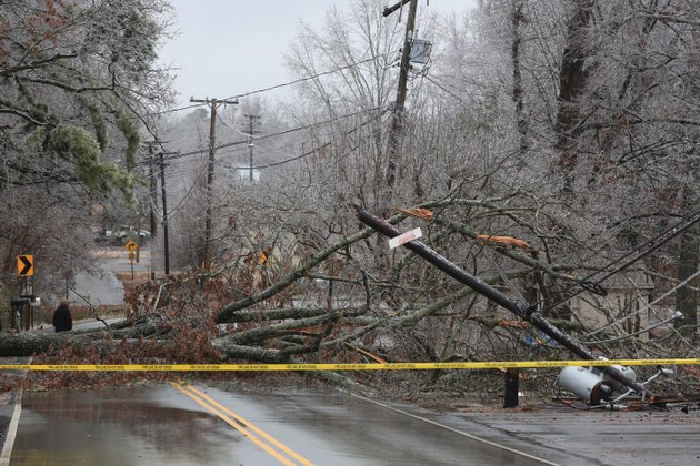 a-large-ice-covered-hardwood-tree-fell-over-and-landed-on-a-power-line-snapping-the-utility-pole-off-and-causing-the-lines-and-transformers-to-land-on-the-street-in-the-10000-block-of-mablevale-pike-in-little-rock-tuesday-feb-4-2013