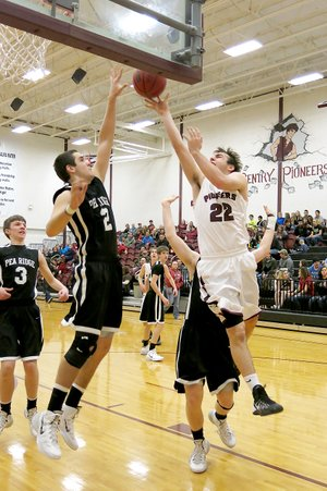 Photo by Randy Moll Gentry junior, Brent Barker, attempts a shot over Pea Ridge junior, Tristan Trundle, in play between the two teams at Gentry on Jan. 28.
